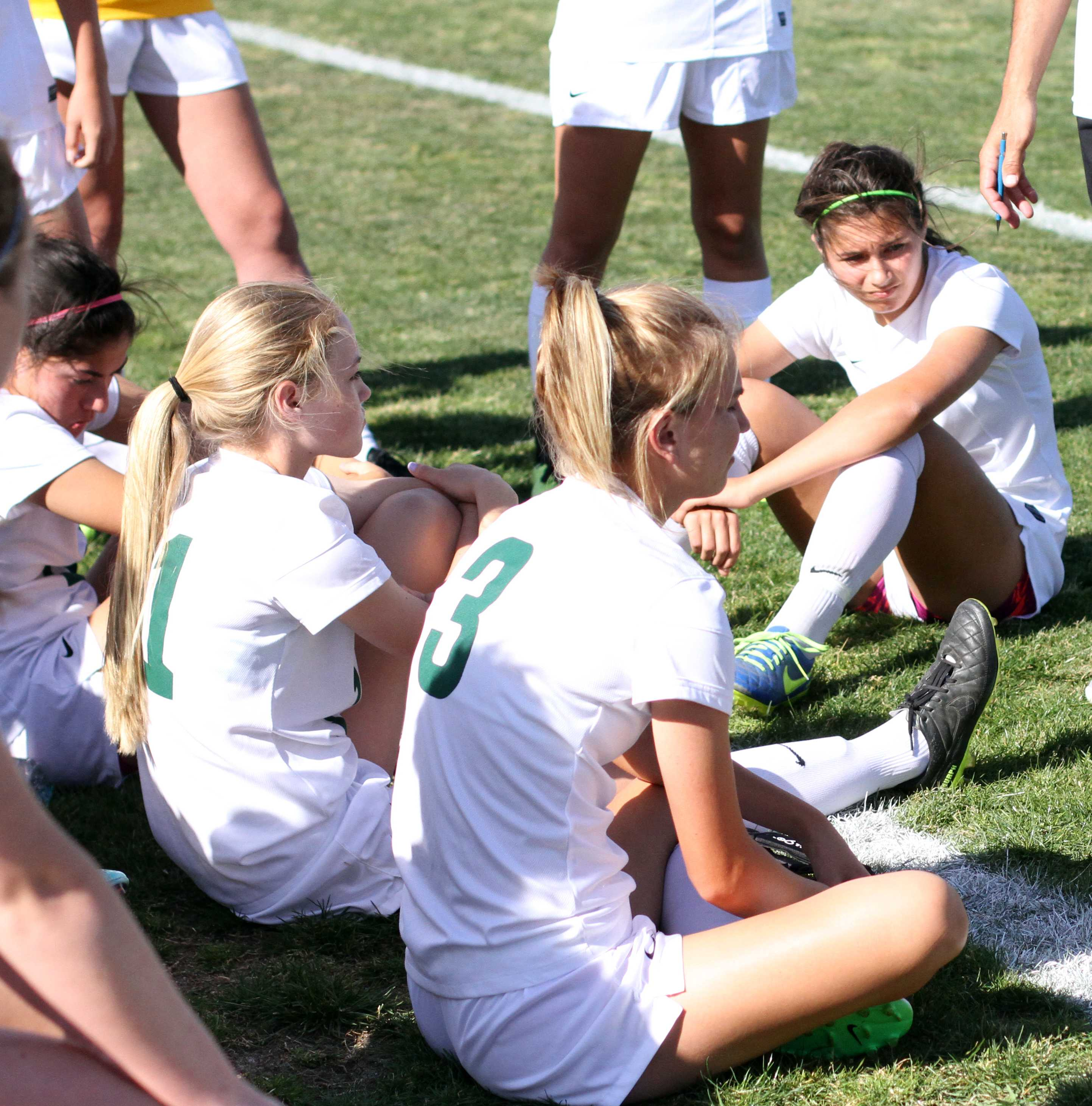 "Along with some of the Girl's Varsity Soccer team, freshman Isabella Perez sits on the floor during a time-out against Folsom. 20 minutes before the game ending with a tie of 1:1, their coach brings them all together to tell them strategies and encouragements for them to play diligently for the remaining time left. ""I must have determination when the game is about to end. I always try to leave it out on the field even if I am tired,"" Perez said. Photo by David Goni"