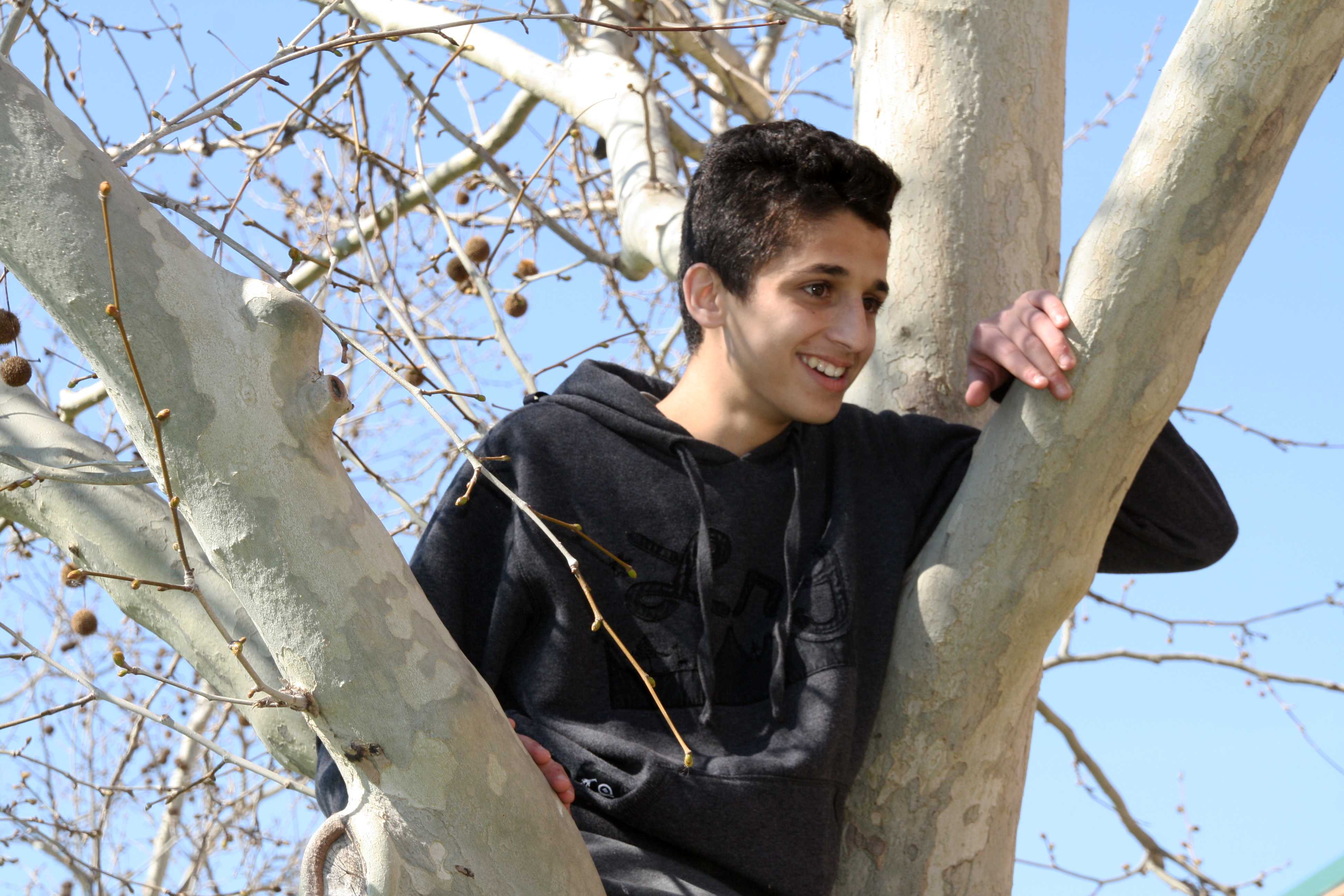 Out shooting for photography freshman Ramzi Taha climbs into a tree to pose  for other students in the class so they could get their shots for the project that they have to turn in soon. For the project they were working on they were required to show different photography compositions Taha climbed the tree in order to model framing. Photo by Hannah Bociek