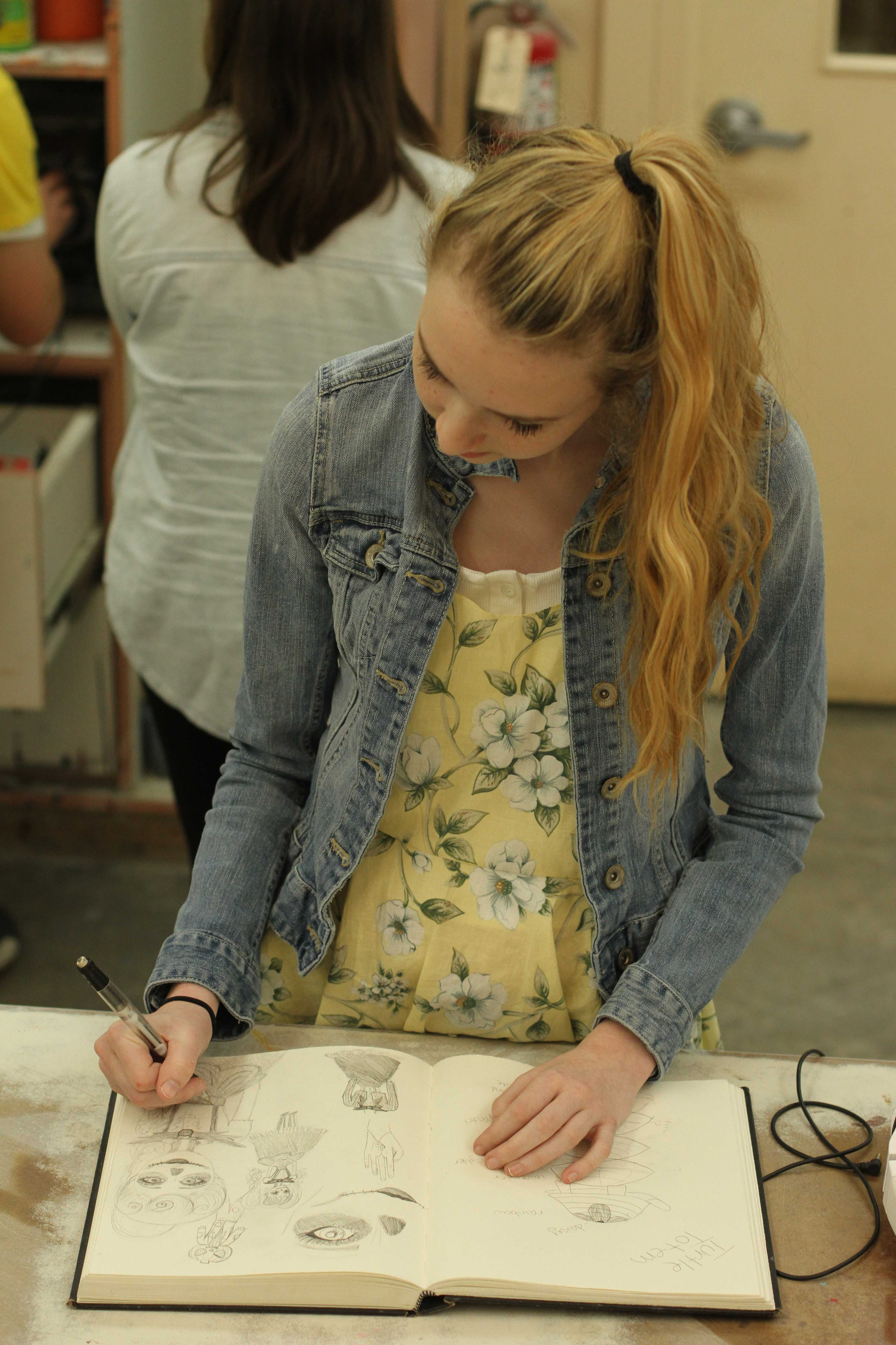 "In Mr. Brad Cordell's Ceramics class third period, sophomore Cassie Hamilton a design for her cosplay draws in her sketchbook. Hamilton planned on attending SacAnime, a smaller, more local version of Comic Con, September 4-6 in a gender bent Jack Skeleton. ""Sewing is pretty difficult but I enjoy that you get to create your own clothes,"" Hamilton said. Photo by Nicole Svistun"