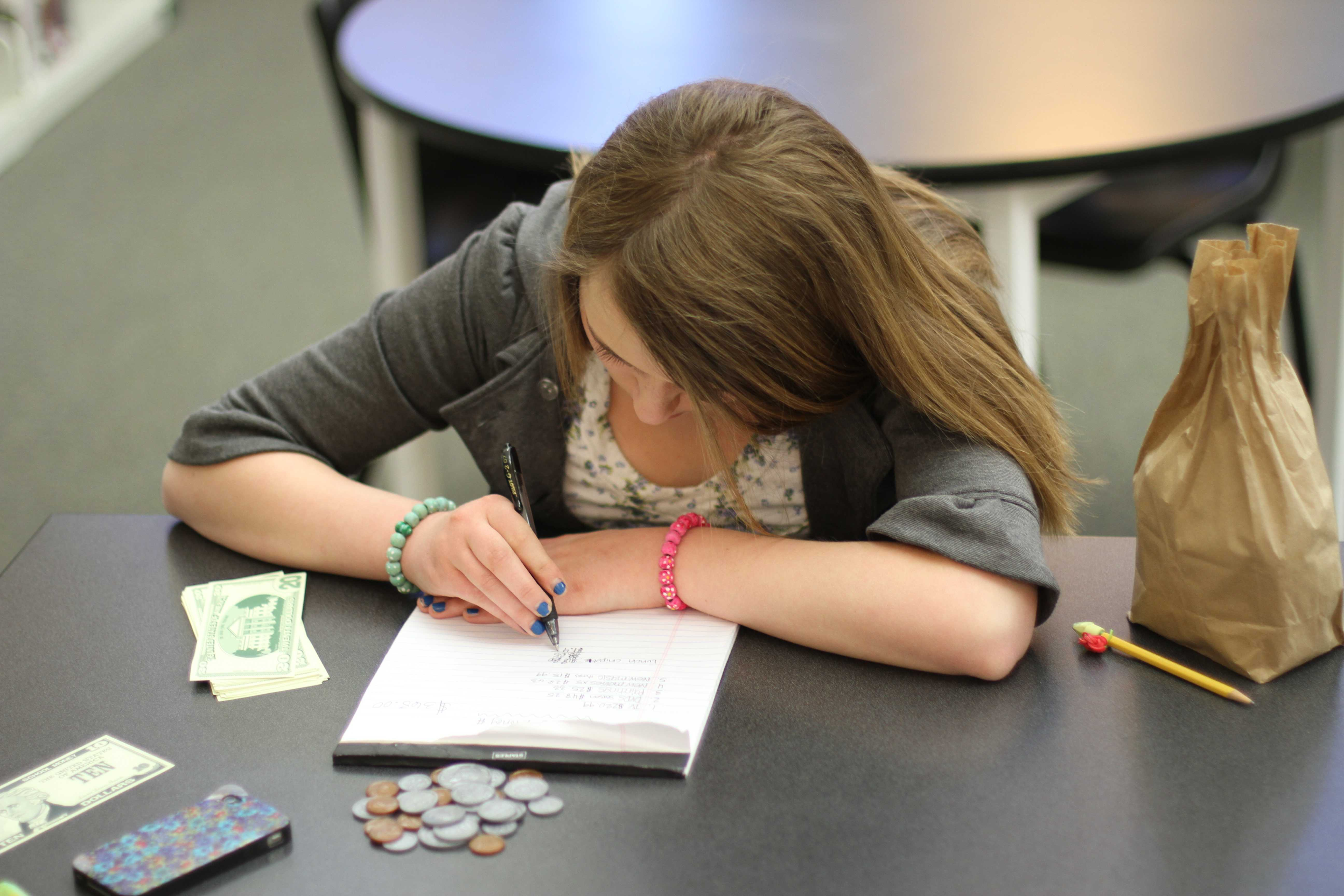 "In the library first period, sophomore Morgan Ransdell works on her math skills. Although math isn't her favorite subject, she practices her money math skills by solving problems and using plastic coins and fake paper money. ""It's to help you get ready for graduation and see if you can get a good degree in math and other school subjects too,"" Ransdell said. Photo by Reese Richmond"