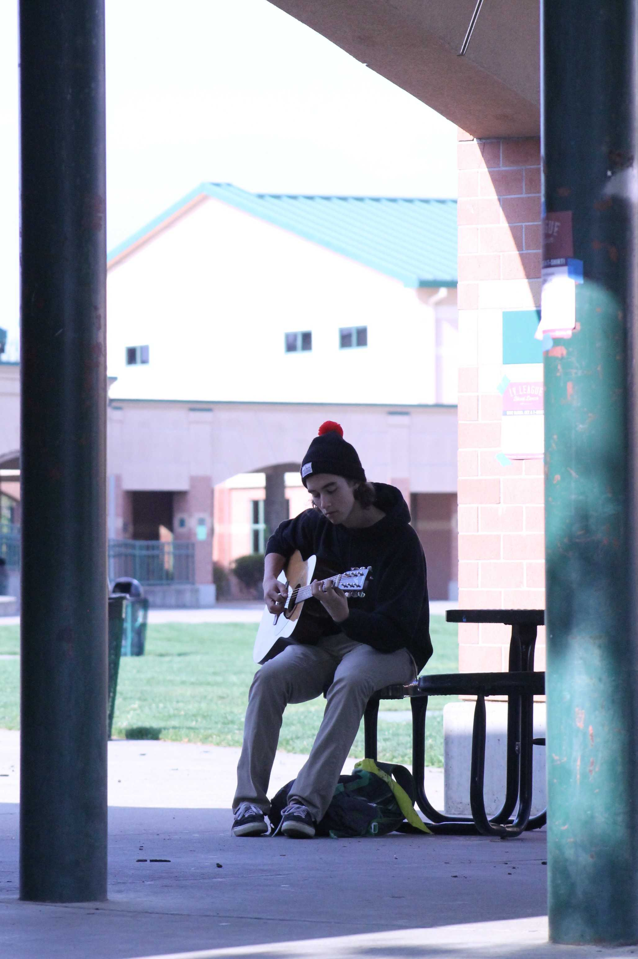 "Although Guitar class can be very loud, senior Maxx Munzel finds a nice place to get away from the sound and focus on his strumming. ""I try to escape the noise of other people playing as much as I can,"" Munzel said. Photo by Sanjna Saini"