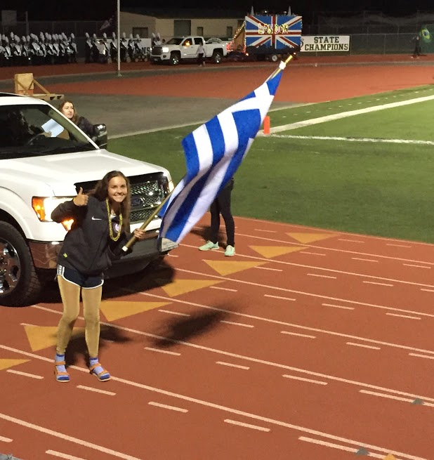 Float Commissioner Meryl Isaacson waves the Greece flag proud as the freshmen are crowned first place at this year's homecoming float competition.